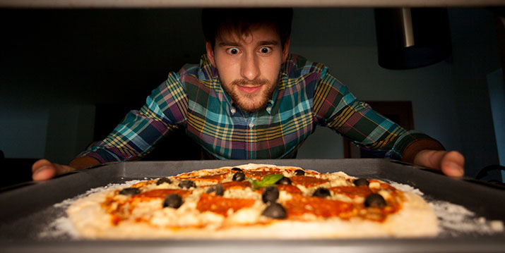 Image of man taking pizza from oven